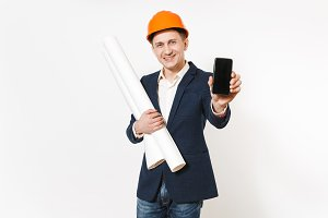 Young dissatisfied businessman in dark suit, protective hardhat holding blueprints plans and mobile phone with blank screen on copy space isolated on white background. Male worker for advertisement.