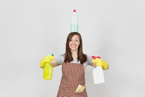 Fun housewife in yellow gloves, striped apron, cleaning rag in pocket on white background. Woman holding in hands, on head bottles with cleaner liquid for washing dishes. Copy space for advertisement.