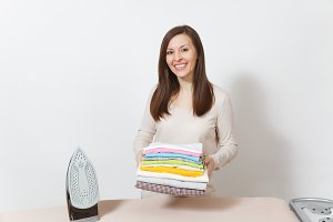 Young attractive smiling housewife in light casual clothes holding family clothing on ironing board with iron. Woman isolated on white background. Housekeeping concept. Copy space for advertising.