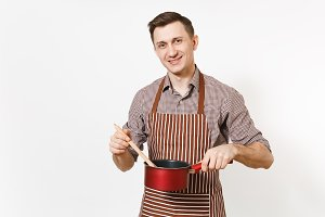 Young smiling man chef or waiter in striped brown apron, shirt holding red empty stewpan, wooden spoon isolated on white background. Male housekeeper or houseworker. Kitchenware and cuisine concept.