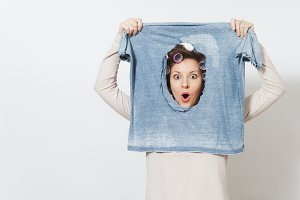 Shocked housewife, curlers on hair in light clothes hold burned ironing shirt, looking through hole made by iron. Woman isolated on white background. Housekeeping concept Copy space for advertisement.