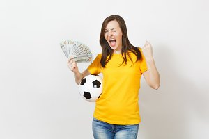 Young fun woman football fan or player in yellow uniform with winner gesture hold bundle cash dollars soccer ball isolated on white background. Sport, play football game, excitement lifestyle concept.