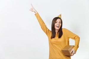 Fun young happy woman in yellow clothes, birthday party hat holding golden gift box with present, celebrating holiday, pointing finger away on white background isolated, copy space for advertisement.
