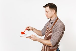 Young man chef in striped brown apron, shirt holds washes white round empty clear plate with red brush for washing dishes isolated on white background. Male housekeeper, houseworker or domestic worker