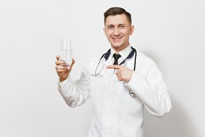 Smiling experienced handsome young doctor man isolated on white background. Male doctor in medical uniform, stethoscope holding glass of clear water. Healthcare personnel, health, medicine concept.