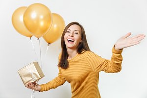 Beautiful European fun young happy woman in yellow clothes with shy charming smile, golden balloons, celebrating birthday, on white background isolated for advertisement. Holiday, party concept.