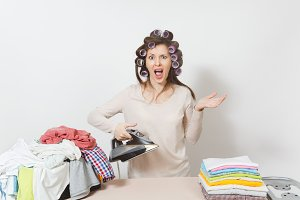 Distressed housewife with curlers on hair in light clothes ironing family clothing on ironing board with iron steam. Woman isolated on white background. Housekeeping concept. Copy space advertisement.