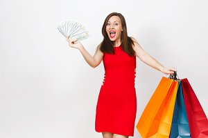 Attractive glamour fashionable young brown-hair woman in red dress holding cash dollars, multi colored packets with purchases after shopping isolated on white background. Copy space for advertisement.