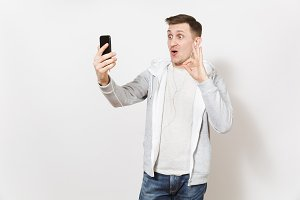 Young handsome man in t-shirt and light sweatshirt with headphones takes himself selfie on mobile phone during call, shows gesture okay isolated on white background. Concept of communication good mood