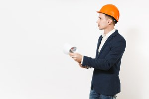 Young handsome businessman in dark suit, protective hardhat holding clipboard with papers document and looking aside on copy space isolated on white background. Male worker for advertisement.