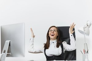 Smiling business woman sitting at the desk, working at computer with modern monitor and documents in office, rejoicing at success, holding hands up on white background, copy space for advertisement