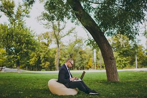 Young successful businessman in white shirt, classic suit, glasses. Man sit on soft pouf, working on laptop pc computer in city park on green lawn outdoors on nature. Mobile Office, business concept.