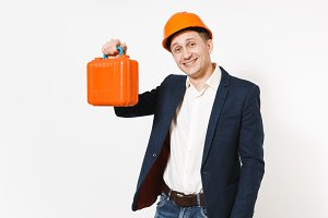 Young handsome smiling businessman in dark suit, protective construction helmet holding case with instruments or toolbox isolated on white background. Male worker for advertisement. Business concept.