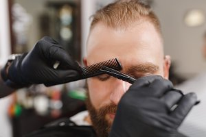 Male professional hairdresser serving client, shearing eyebrows with scissors. Ginger stylish young man with thick big beard and short hair getting trendy haircut in black cape. Light barber shop room
