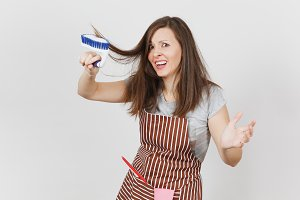 Young fun crazy dizzy loony wild housewife in striped apron with squeegee, pink gloves in pocket isolated on white background. Mad woman comb out tousled brown hair by brush for cleaning. Copy space.