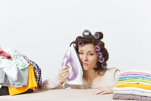 Distressed housewife, curlers on hair in light clothes ironing family clothing on ironing board, put iron to face. Woman isolated on white background. Housekeeping concept. Copy space advertisement.
