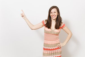 Beautiful young brunette girl in light beige and pink patterned dress smiling, holding hand on waist and pointing index finger aside on copy space isolated on white background. Concept of good mood.