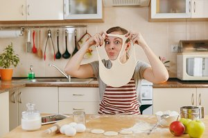 A young funny cheerful and smiling woman puts on a dough with holes on her face and has fun in the kitchen. Cooking home. Prepare food.