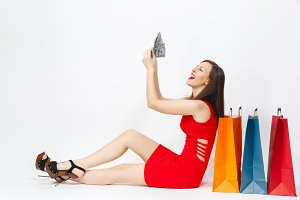 Beautiful fun glamour fashionable young woman in red dress sitting with cash dollars, multi colored packets with purchases after shopping isolated on white background. Copy space for advertisement.