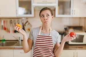 A young confused and pensive woman in an apron decides to choose a red or yellow tomato in the kitchen. Dieting concept. Healthy lifestyle. Cooking at home. Prepare food.