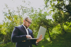 Young successful smart businessman in white shirt, classic suit, glasses. Man standing and working on laptop pc computer in city park outdoors on nature background. Mobile Office, business concept.