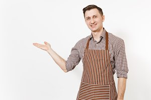 Young man chef or waiter pointing hand aside on copy space in striped brown apron, shirt isolated on white background. Male housekeeper or houseworker looking camera. Domestic worker for advertisement