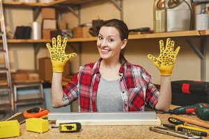 Beautiful caucasian young brown-hair woman in plaid shirt, gray T-shirt, yellow gloves spreading hands, working in carpentry workshop at wooden table place with piece of iron and wood, different tools