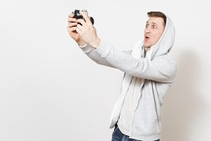 Young handsome excited student in t-shirt and light sweatshirt with hood with headphones photographs himself on retro camera in studio on white background. Concept of photography, hobby