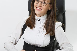 Beautiful smiling brown-hair business woman in suit and glasses sitting at the desk, working at computer with modern monitor with documents in light office, looking at the camera on white background
