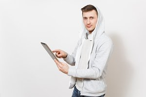 Young handsome man tudent in t-shirt and light sweatshirt with hood with headphones holds tablet pc computer in hands, using it and looks at camera isolated on white background. Concept of technology