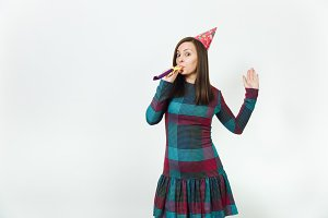 Beautiful caucasian fun young happy woman in plaid dress and birthday party hat with shy charming smile and pipe, celebrating and enjoying holiday on white background isolated for advertisement.
