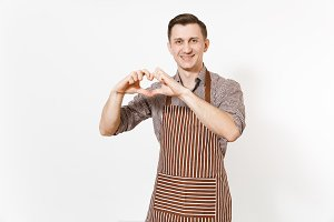 Smiling man chef or waiter in striped brown apron, shirt showing hands shape of heart isolated on white background. Male housekeeper or houseworker - looking camera. Domestic worker for advertisement.