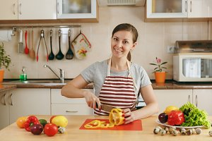 A young attractive woman in an apron cuts vegetables for salad with a knife in the kitchen. Dieting concept. Healthy lifestyle. Cooking at home. Prepare food.