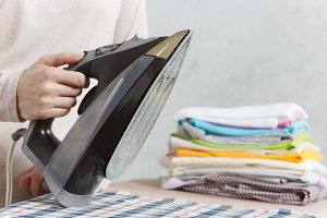 Close up cropped photo woman hand holding iron. Housewife in light clothes ironing checkered shirt, clothing on ironing board with iron. Housekeeping concept. Copy space for advertisement.