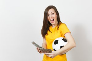 European young fun woman, football fan or player in yellow uniform holding bunch of money banknotes, soccer ball isolated on white background. Sport, play football game, excitement lifestyle concept.
