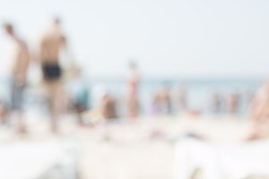 Tourists on the beach, blurred photo. Summer Holiday Vacation Concept.