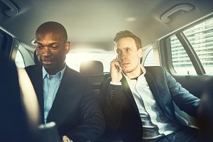 Two businessmen being driven through the city in car