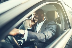 African businessman sitting in a car talking on his cellphone