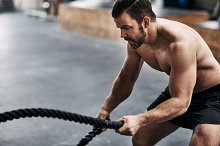 Fit young man exercising with ropes during a gym workout by Stefan Dahl in Sports