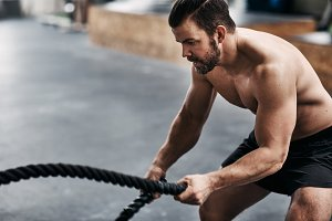 Fit young man exercising with ropes during a gym workout