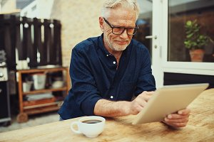 Smiling senior man drinking coffee and using a digital tablet