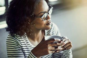 Smiling African woman thinking while drinking coffee in a cafe