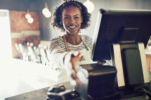 Friendly African entrepreneur extending a handshake in her cafe