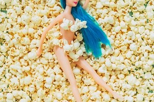 doll laying on a bed of popcorn