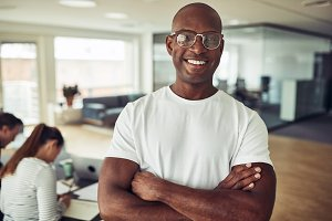 African businessman smiling with colleagues at work in the background