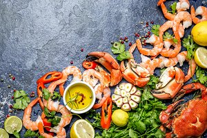 Fresh raw seafood - shrimps and crabs with herbs and spices on dark gray background. Copy space