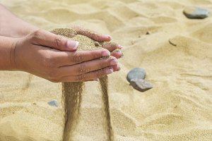 Female hands with sand on the beach.