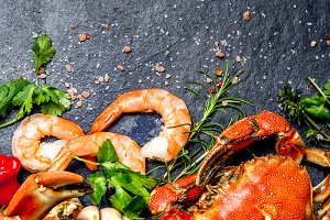 Fresh raw seafood - shrimps and crabs with herbs and spices on dark gray background. Copy space. Vertical