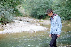 Explorer man walking by the river.