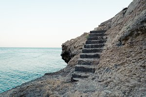 Stone stairs on the rock to the blue sea